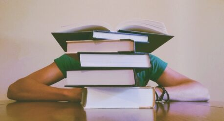 Student behind pile of textbooks