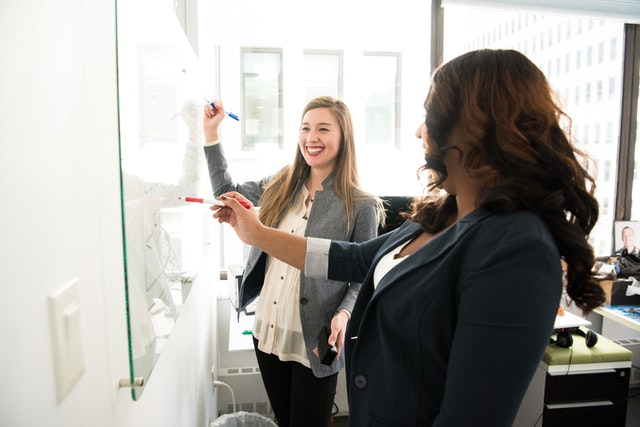 two women in front of white board at the office