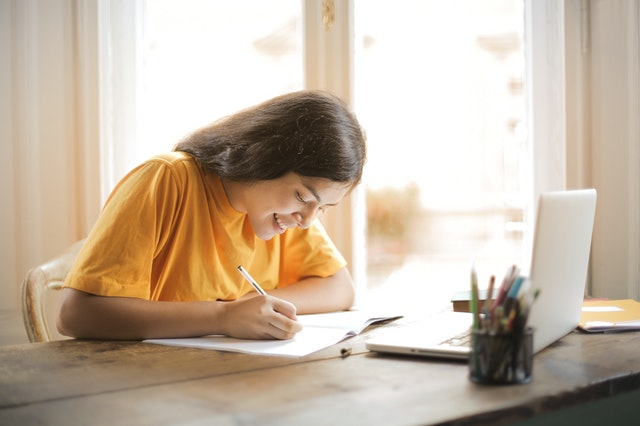 Student studying at desk in yellow shirt
